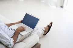 Man Using Laptop On Sofa Stock Images