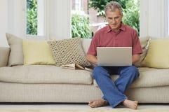 Man Using Laptop On Sofa Stock Image