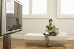 Man Using Laptop On Sofa In Modern Apartment Stock Images