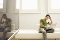Man Using Laptop On Sofa In Modern Apartment Stock Image
