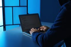 Man using laptop at table in dark room. Criminal offence. Man using laptop at table in dark room, closeup. Criminal offence royalty free stock photos