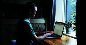 Man using laptop at table. At home stock footage