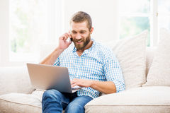 Man using laptop while talking on mobile phone in living room Royalty Free Stock Photography