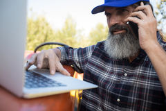 Man using laptop while talking on mobile phone. In olive farm Stock Photo