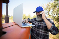 Man using laptop while talking on mobile phone. In olive farm Stock Image