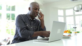 Man Using Laptop And Talking On Phone In Kitchen At Home stock video footage