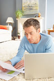 Man Using Laptop To Manage Bills Laying On Rug Stock Image