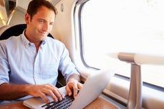 Man Using Laptop On Train Stock Photography