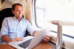 Man Using Laptop On Train Stock Image