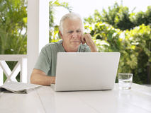 Man Using Laptop At Verandah Table Royalty Free Stock Photos