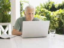 Man Using Laptop At Verandah Table Stock Image