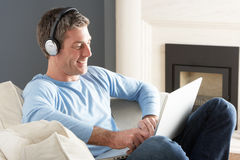 Man Using Laptop Wearing Headphones Relaxing Stock Photo
