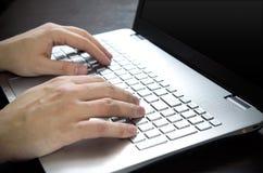Man using laptop with white keyboard Stock Image