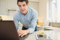 Man using laptop wirth smartphone and tablet. Man using laptop with smartphone and tablet in kitchen Stock Photo