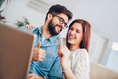 Man using laptop and woman holding credit card. Man using laptop and women holding credit card. Young couple shopping online with credit card at hom Royalty Free Stock Photography
