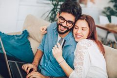 Man using laptop and woman holding credit card. Man using laptop and women holding credit card. Young couple shopping online with credit card at hom Royalty Free Stock Photos