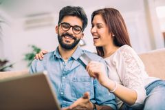 Man using laptop and woman holding credit card. Man using laptop and women holding credit card. Young couple shopping online with credit card at home Royalty Free Stock Photos