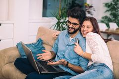 Man using laptop and woman holding credit card. Man using laptop and women holding credit card. Young couple shopping online with credit card at home Stock Photo