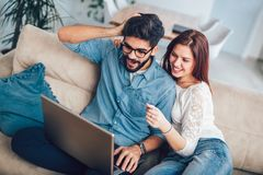Man using laptop and woman holding credit card. Man using laptop and women holding credit card. Young couple shopping online with credit card at home Royalty Free Stock Photography