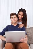 Man using laptop with woman in living room Stock Photo