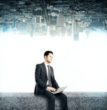 Man using laptop. Young businessman using laptop on upside down city background Royalty Free Stock Photo