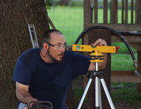 Man Using Laser Level. Man aiming laser beam on level, wearing safety glasses stock image