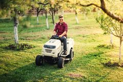 Man using lawn mower and cutting grass during landscaping works. Male using lawn mower and cutting grass during landscaping works Stock Photography