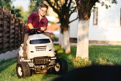 Man using lawn tractor and cutting grass in garden during weekend time. Portrait of man using lawn tractor and cutting grass in garden during weekend time Royalty Free Stock Image