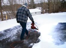 Man using leaf blower to clear snow from driveway. A home owner uses a leaf blower to remove a light powdery snow before it turns to ice on his driveway stock photo