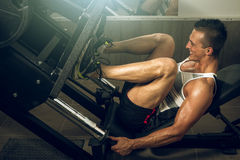 Man using leg press in gym Stock Photo