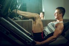 Man using leg press in gym Stock Photography