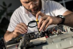 Man using magnifier while. Fixing pc stock images