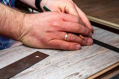 Man using measuring elbow and pencil while installing new wooden laminate flooring at home. stock images