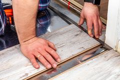 Man using measuring elbow and pencil while installing new wooden laminate flooring at home. Man using measuring elbow and pencil while installing new wooden stock photography