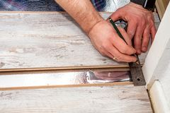 Man using measuring elbow and pencil while installing new wooden laminate flooring at home. Man using measuring elbow and pencil while installing new wooden royalty free stock photo