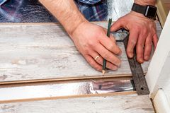 Man using measuring elbow and pencil while installing new wooden laminate flooring at home. Man using measuring elbow and pencil while installing new wooden stock photo