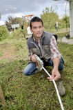 Man using a measuring tape in the garden stock images