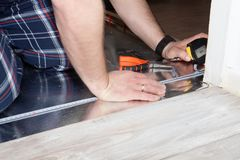 Man using measuring tape and pencil while installing new wooden laminate flooring at home. stock photos