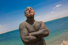 A man using medical mud, standing at the sun. On the shores of the Dead Sea Stock Photo