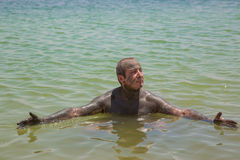 A man using medical mud, swim in the Dead Sea Stock Photos