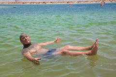 A man using medical mud, swim in the Dead Sea, Israel. Mud treatment on Dead sea Stock Image