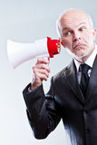 Man using a megaphone with ears instead of mouth Royalty Free Stock Photo