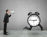 Man using megaphone shouting running clock with human legs Stock Photo