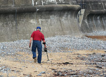 Man using metal detector on a beach. Stock Photo