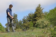 Man using metal detector. A man searching for buried treasure, ancient coins and historic artefacts with metal detector stock photo