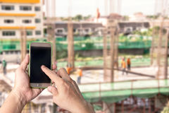 Man using mobile  mobile smart phone with blur construction back Royalty Free Stock Photography