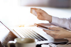 Man using mobile payments with credit card for online shopping on laptop background. M-banking Stock Photos