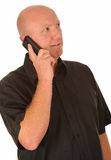 Man using mobile phone. Bald man in brown shirt smiling while  using a mobile phone isolated on white background Stock Image