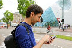 Man using mobile phone app in modern urban city street. Young caucasian man holding smartphone for business work. stock images