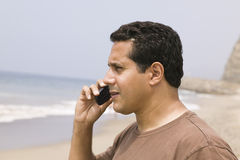 Man using mobile phone on beach Royalty Free Stock Images